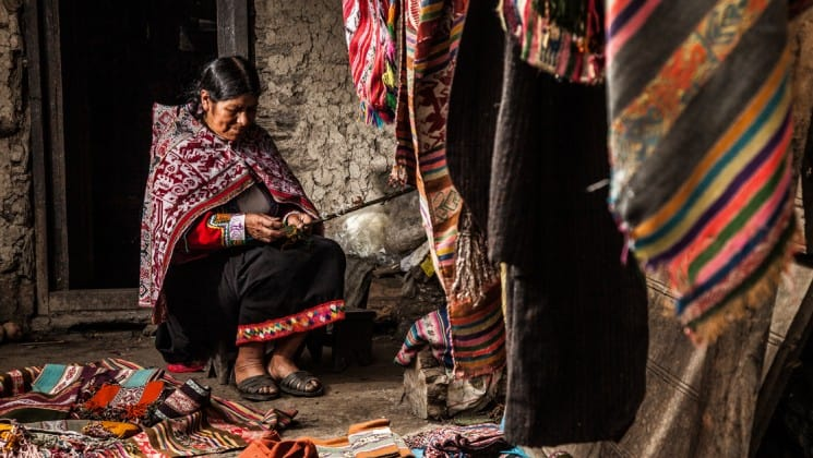 a peruvian woman sits and weaves on sacred valley & lares adventure to machu picchu land tour
