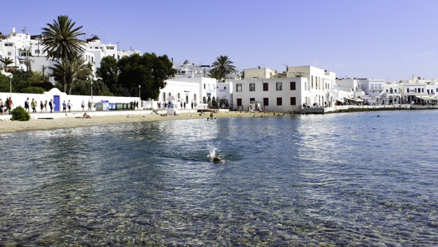 Greek town of Folegandros with white building lining the beach shores and a swimmer in the blue waters.