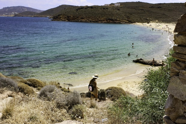 Traveler hiking down to white sandy beach in Greece.