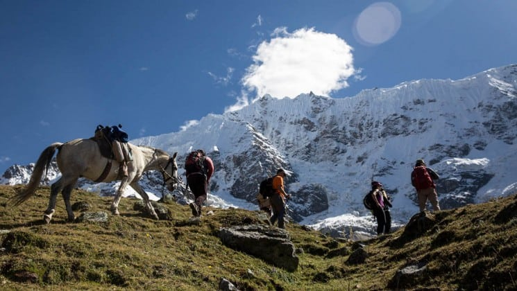 several hikers and a horse approach ridge on salkantay trek to machu picchu