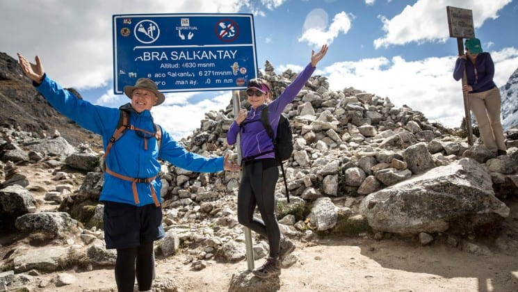 hikers pose by sign on mountaintop on salkantay trek to machu picchu