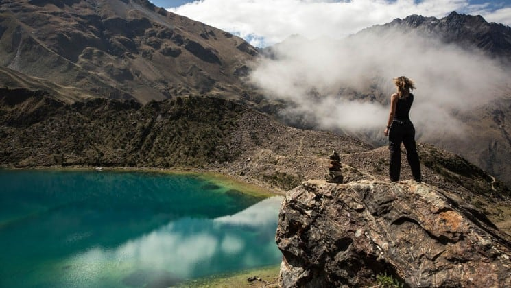 woman at overlook point above mountain lake on salkantay trek to machu picchu