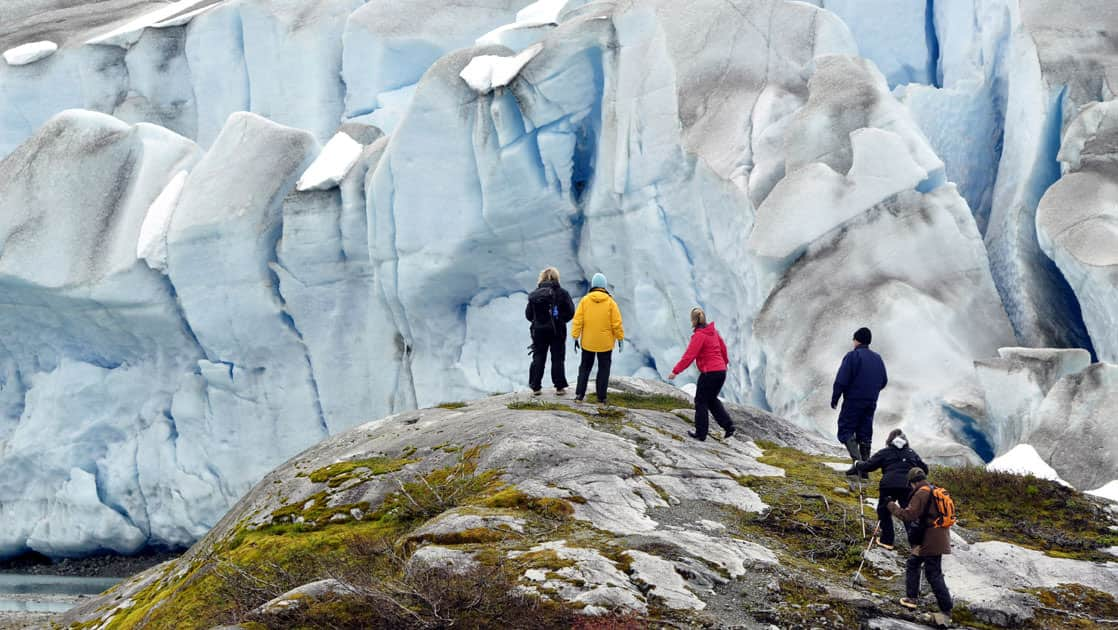 alaska adventure travelers walking along a rocky hill with a large glacier in the background