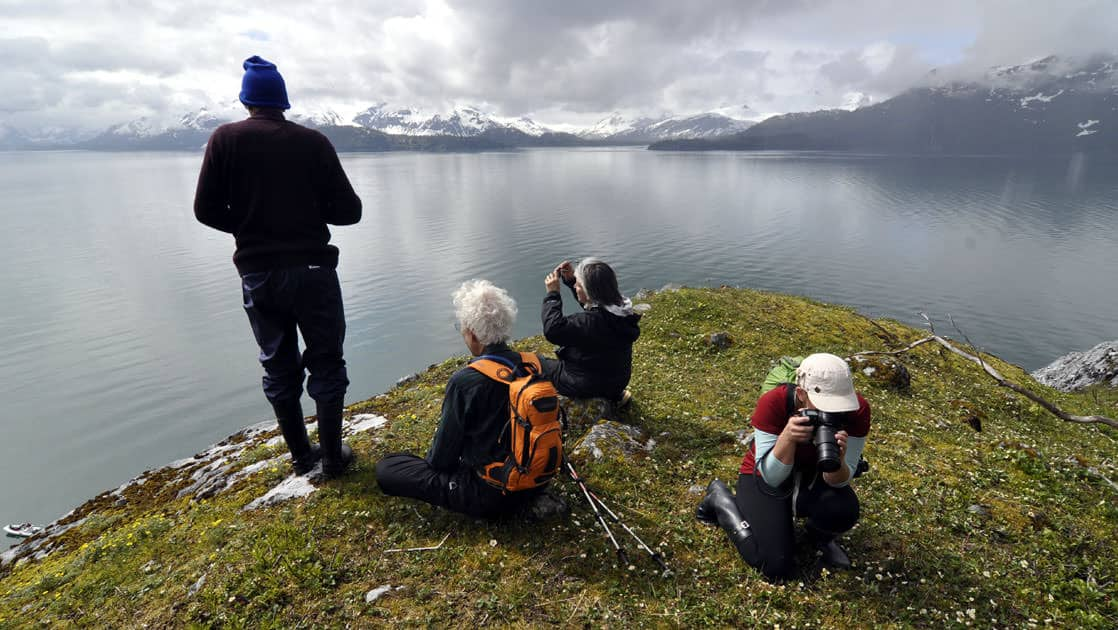 alsaka adventure travelers sit on a grassy cliff taking pictures with calm water below them and clouds in the distance