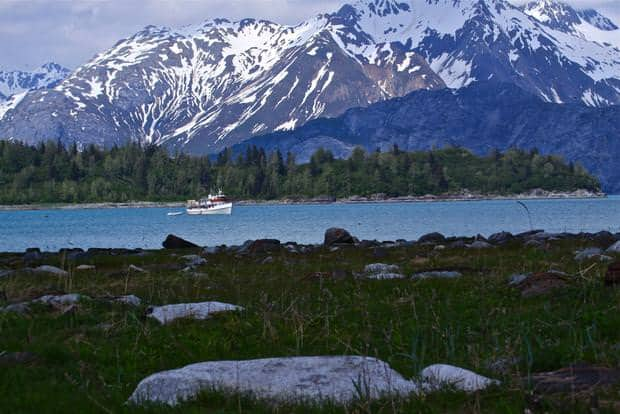 The small ship sea wolf cruising past tall mountains in Alaska.