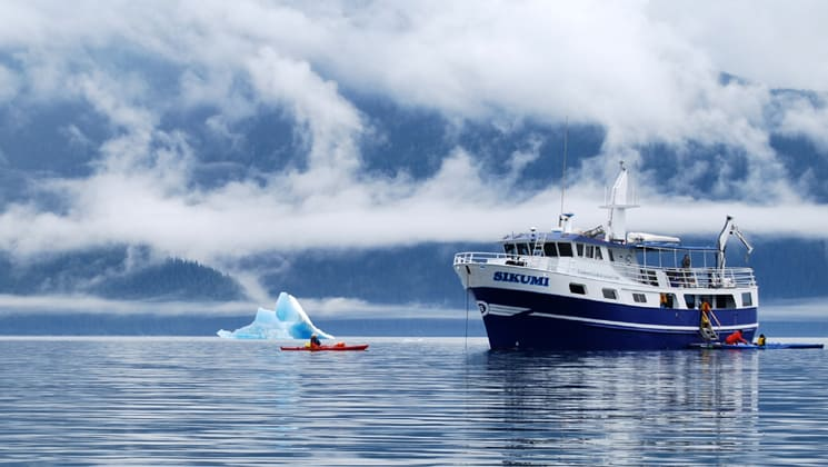 sikumi small ship anchored while an adventure traveler kayaks in front of an iceberg on a misty day in alaska