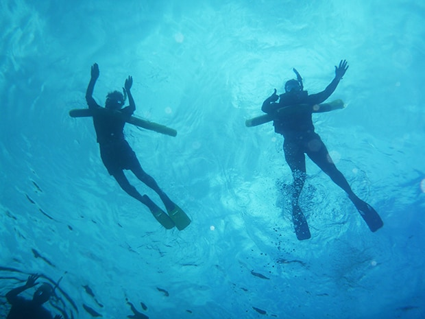 Couple snorkeling together on a romantic small ship cruise in Hawaii.