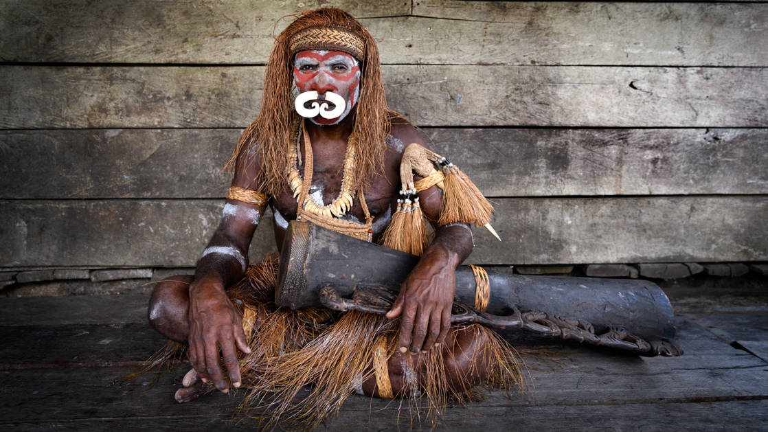 West Papuan tribesman sits with a wooden drum in front of a weathered wood-plank wall during the Spice Islands & Raja Ampat small ship cruise in Indonesia.