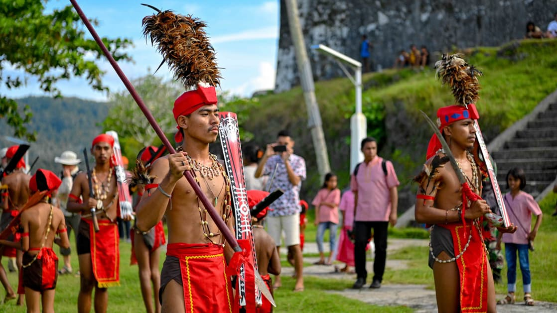 Men in red loincloths and red headbands with tall brown feathers march in order beside a stone fort on a sunny day during the Spice Islands & Raja Ampat small ship cruise in Indonesia.