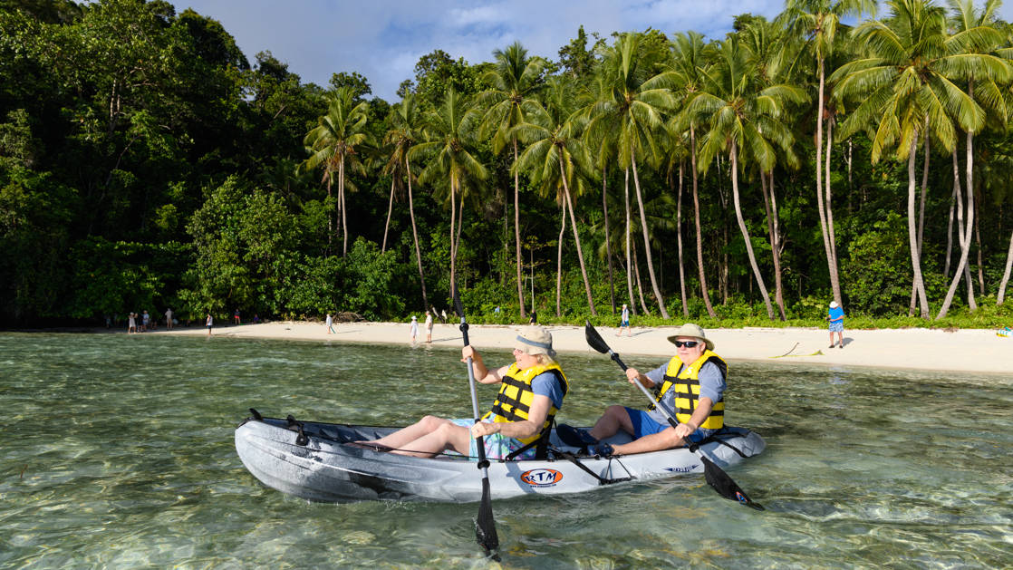 Man & woman paddle through clear, shallow waters on a sit-on-top, tandem kayak with white-sand beach and palm trees in the background during the Spice Islands & Raja Ampat small ship cruise in Indonesia.