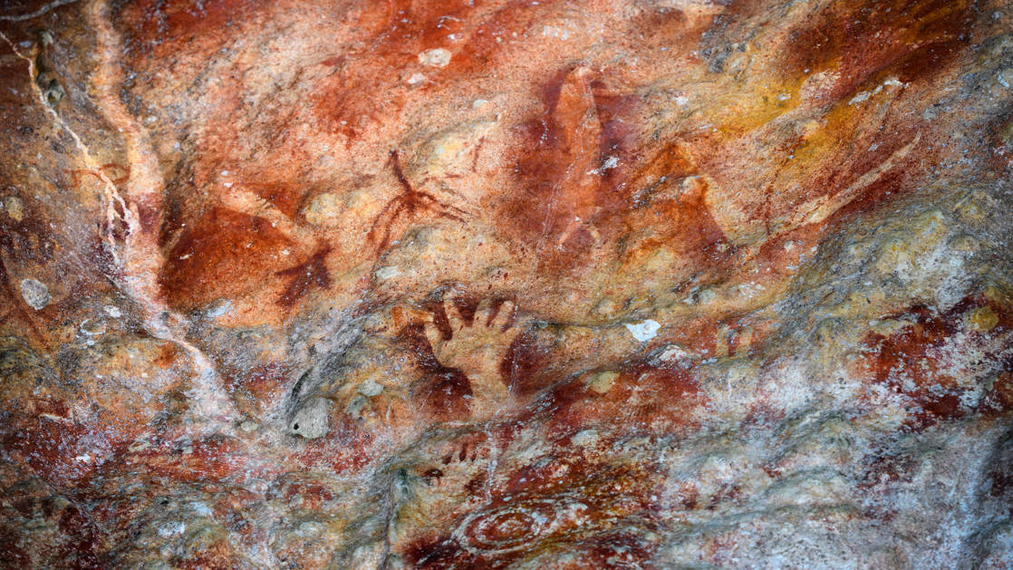 Petroglyphs of red, beige & orange as seen on the Spice Islands & Raja Ampat small ship cruise in Indonesia.