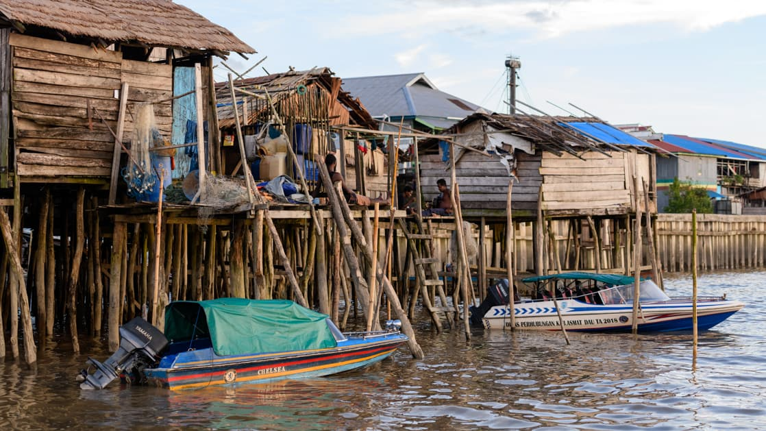 Indonesian village standing above the water on stilts with 2 small boats in the foreground as seen on the Spice Islands & Raja Ampat small ship cruise in Indonesia.