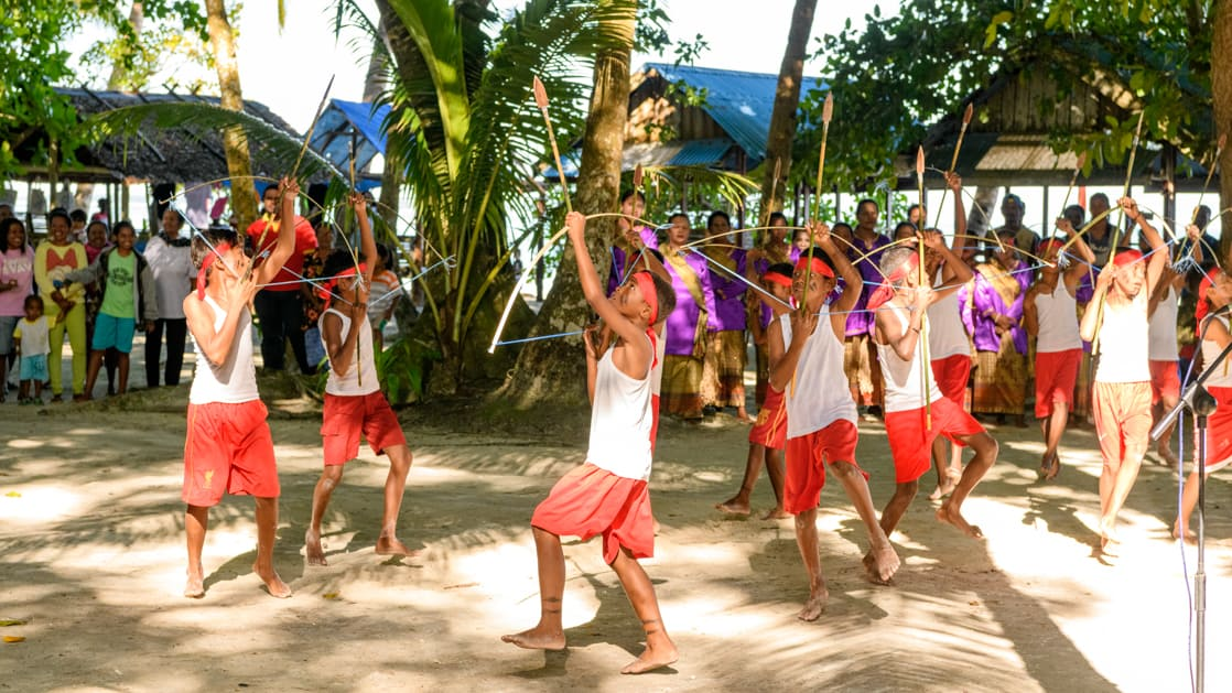 Village children welcome guests with a dance on the sand involving bows and arrows during the Spice Islands & Raja Ampat small ship cruise in Indonesia.