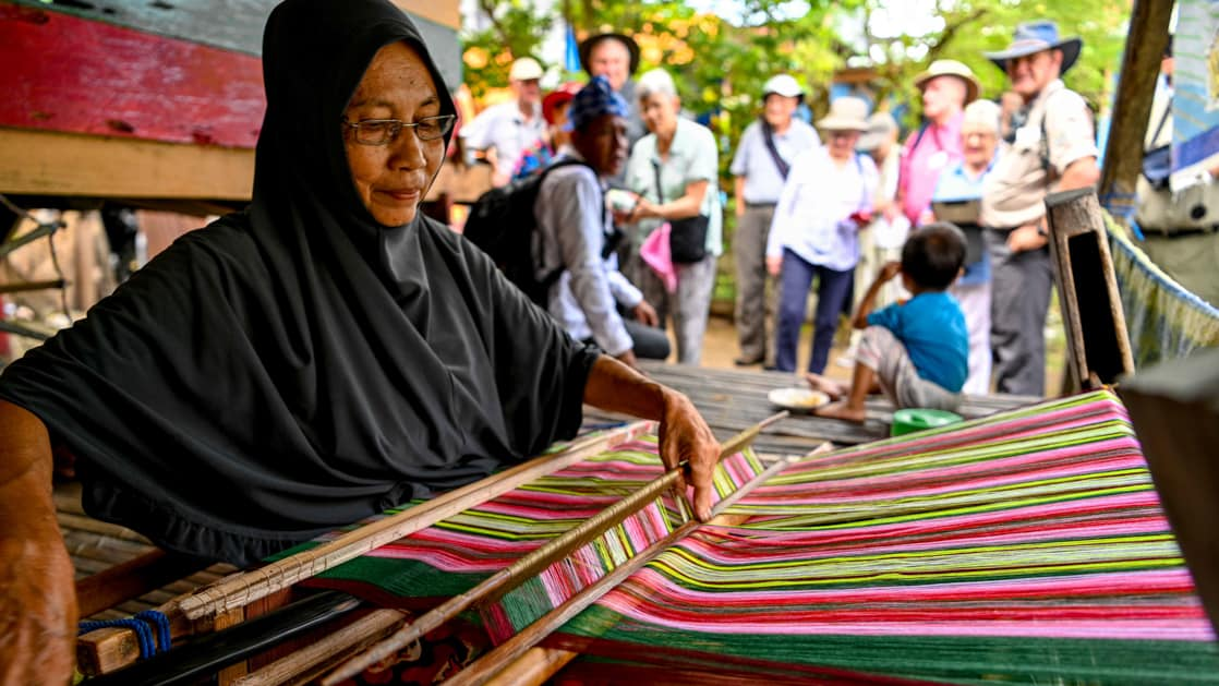 Woman sits at a loom and weaves brightly colored threads at a market during the Spice Islands & Raja Ampat small ship cruise in Indonesia.