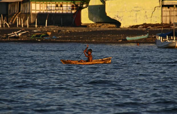 Small child canoeing in the water off the shoreline of a Indonesian town.
