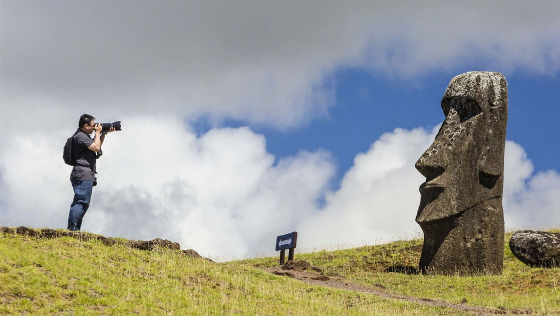 solo traveler takes a photograph of a rapa nui statue in easter island chile while standing on a grassy knoll on a partly sunny day