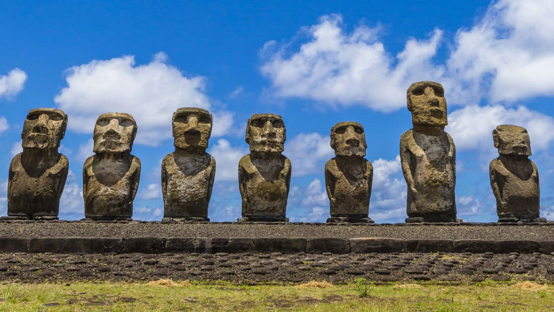 line of moai statues in chile all facing the same direction on a sunny day with clouds above