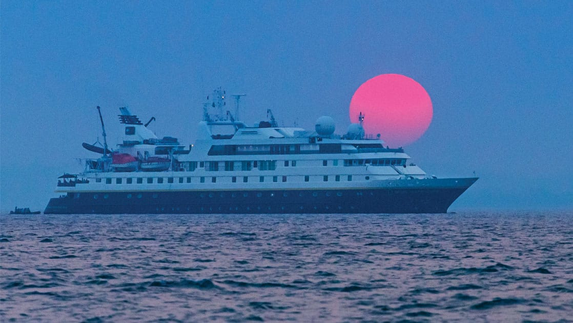 national geographic small ship cruising chile waters at night with a blood red moon behind it