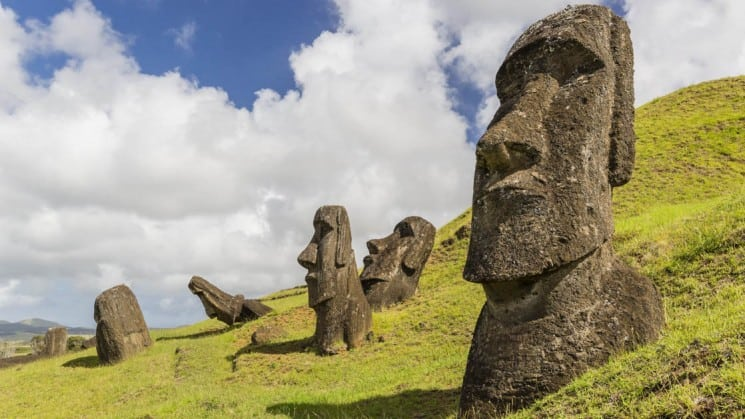 a grassy hillside in easter island chile with several moai statues sitting on it with puffy clouds behind them