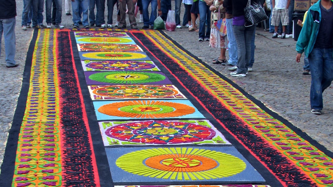 A large colorful tapestry layed out on the ground with people surrounding it in Guatemala.