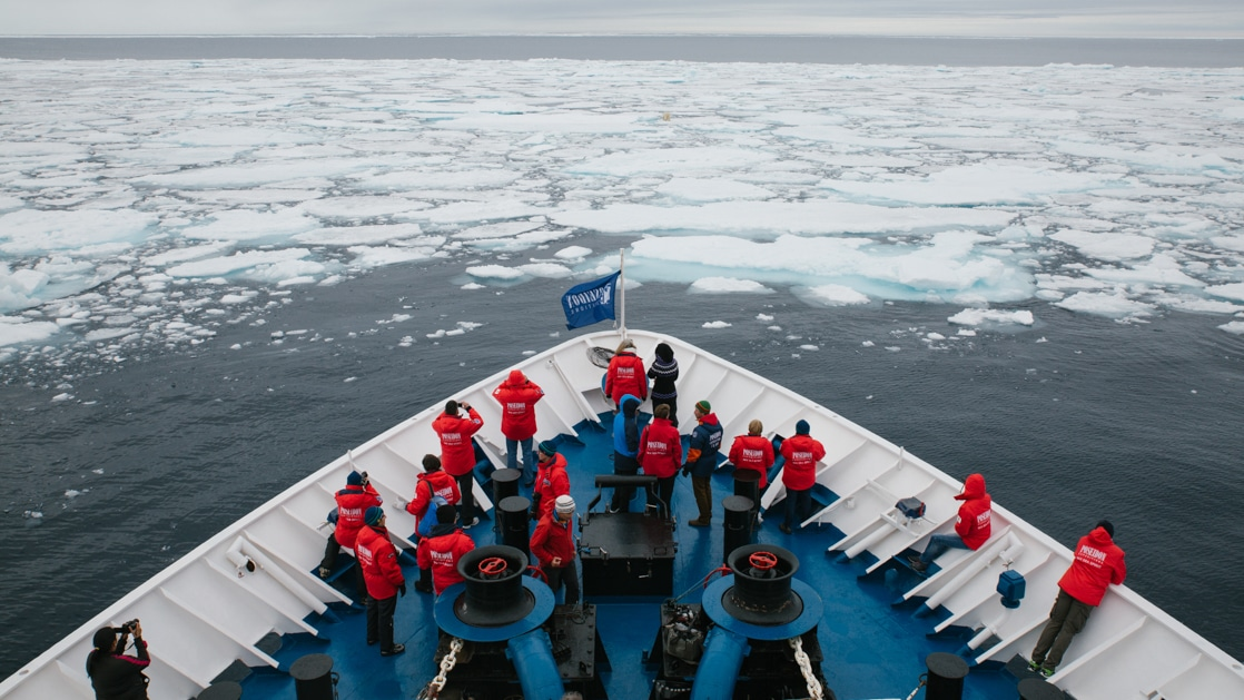 passengers at bow of ship approaching float ice in arctic