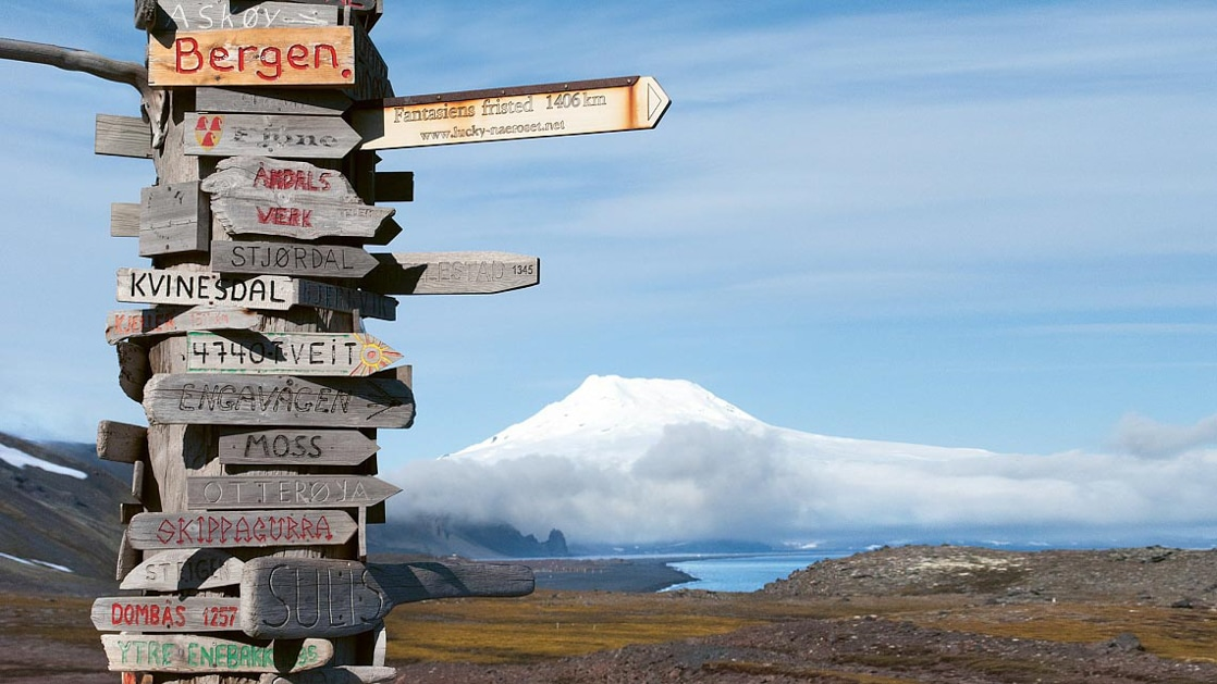 Tall wooden sign with markers pointing to major Northern Europe cities such as Bergen, Norway, set on a green tundra on a sunny day.