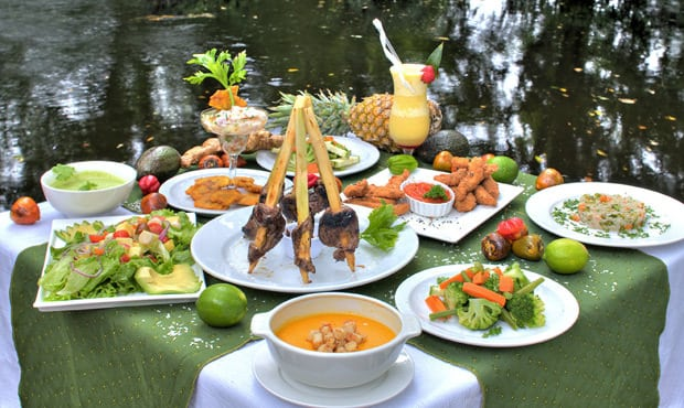 Table of Costa Rican food set outside next to water.