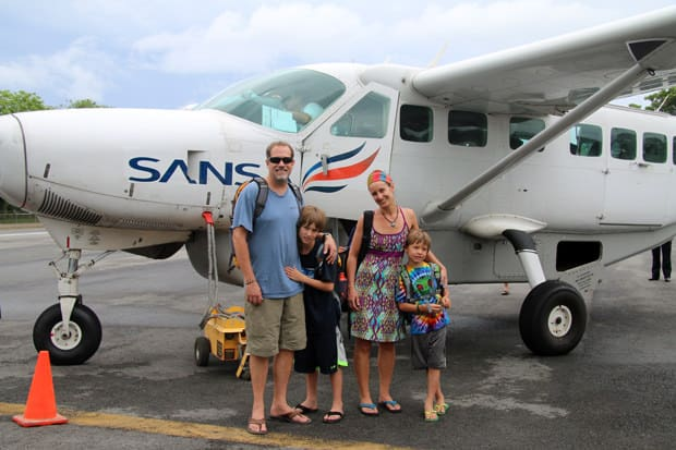 A family of travelers in front of a Costa Rican plane.