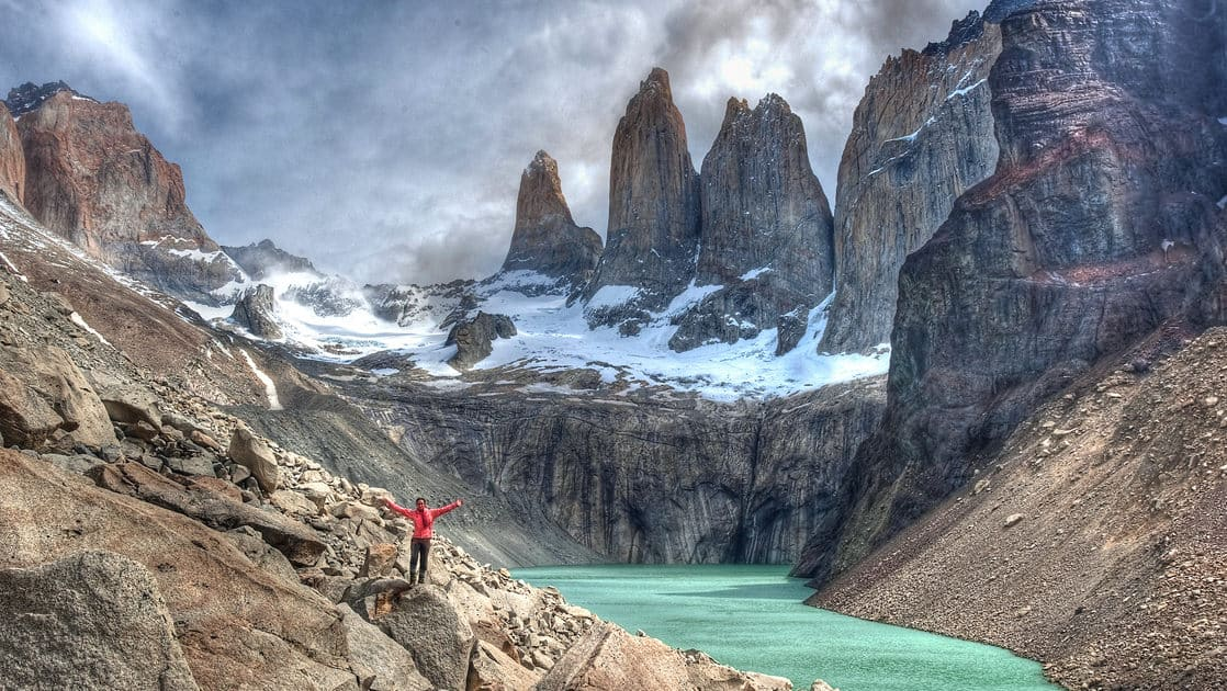 Hiker with arms up in the air in front of the green lake with the Cordillera del Paine mountains behind in Chile