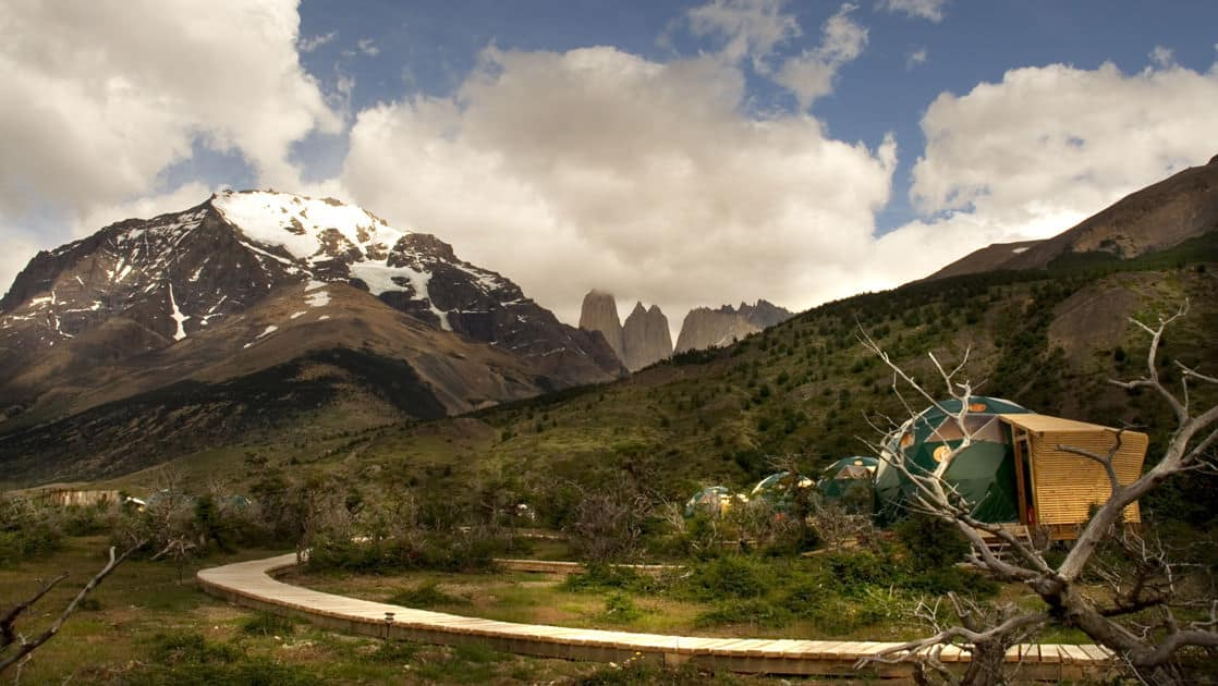 Boardwalk path to several glamping domes at the Patagonia Eco camp surrounded by mountains in chile