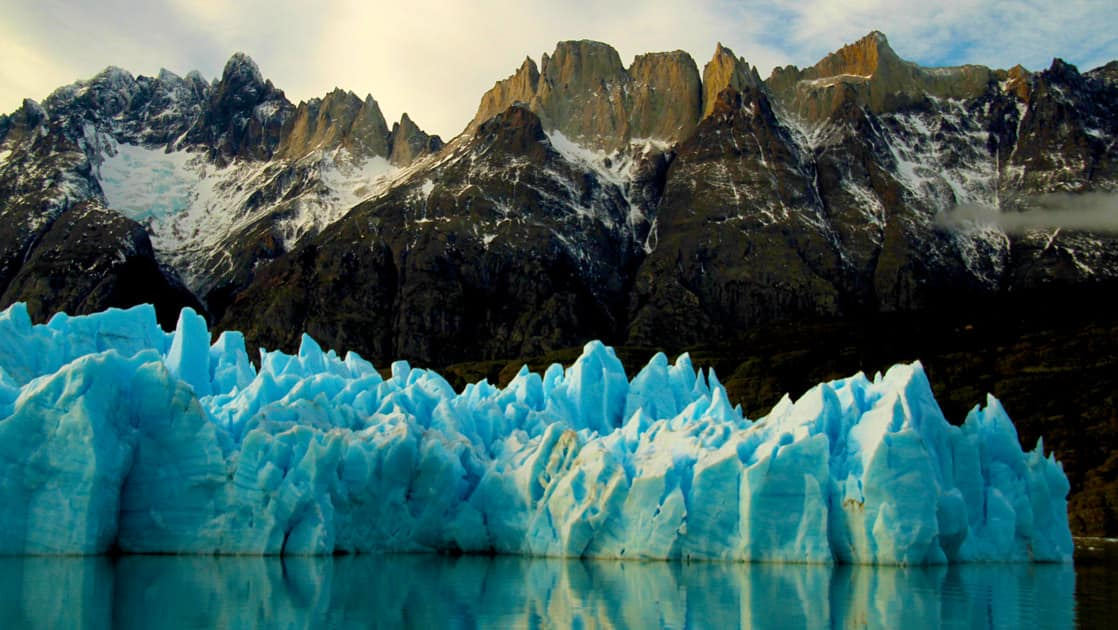 Close up of the grey glacier appearing very blue and with mountains behind in chile's patagonia