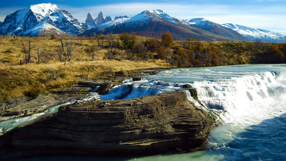 Waterfalls cascading over a plateau of rocks in Patagonia with the mountains behind