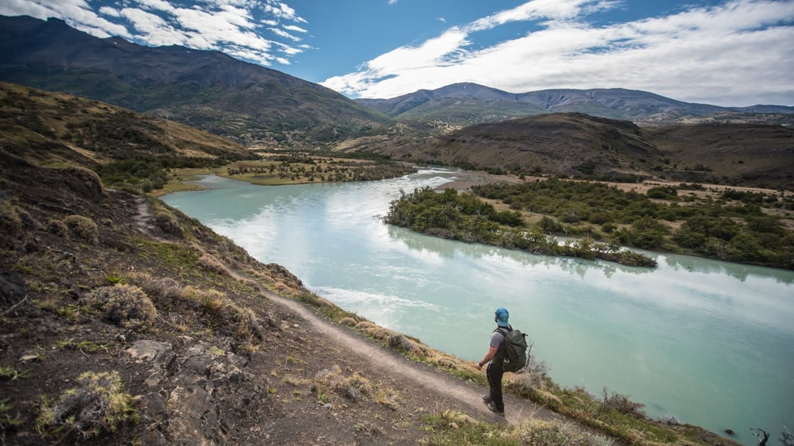 Man stands on smooth dirt trail overlooking a milky turquoise glacial lake on a sunny day during the Torres Del Paine Trek.