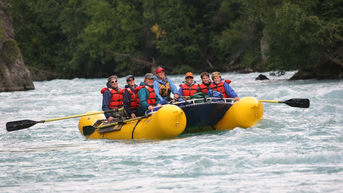 a group sits in red life jackets in a yellow river raft on the penia river while on the ultimate Alaska adventure land tour