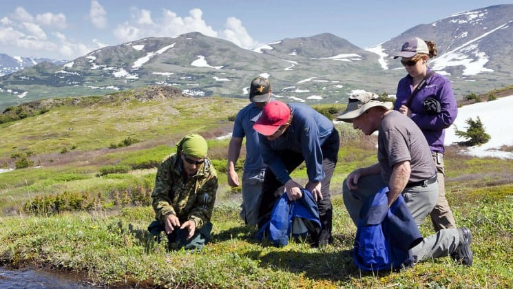 group of hikers crouching near river on ultimate alaska adventure trip