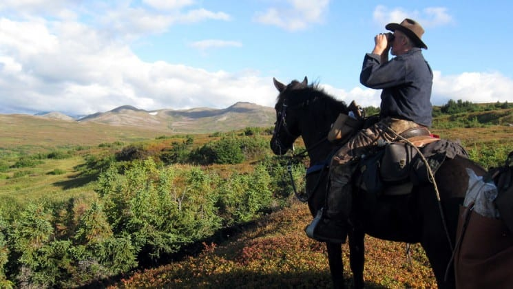 man on horseback looking through binoculars to epic landscape on ultimate alaska adventure trip