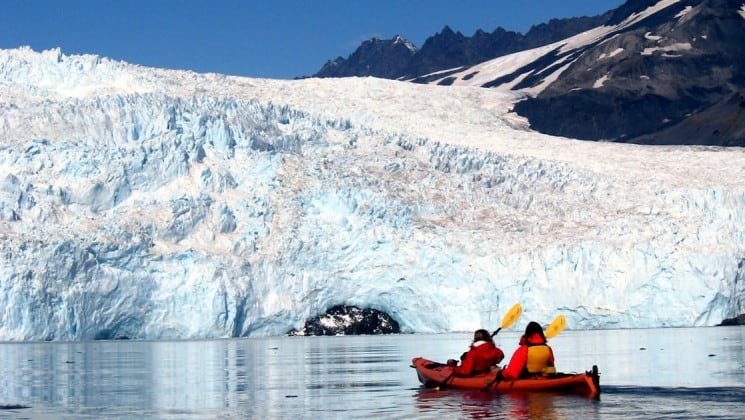 two people in kayak near huge glacier on ultimate alaska adventure