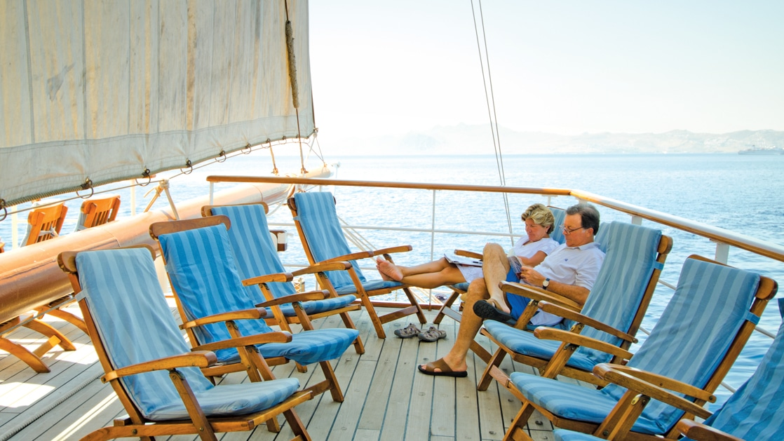 Man & woman sit on teak deck chairs lined with bright blue padding, reading under full sail of the Sea Cloud ship in the Mediterranean.