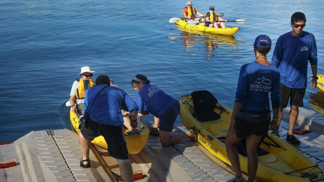 small ship cruise staff helping passengers load into kayaks on the back deck of the vessel into serene water on a sunny day in costa rica