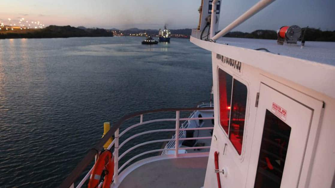 looking past the front cabin and bow of a costa rica small ship at the panama canal at dusk