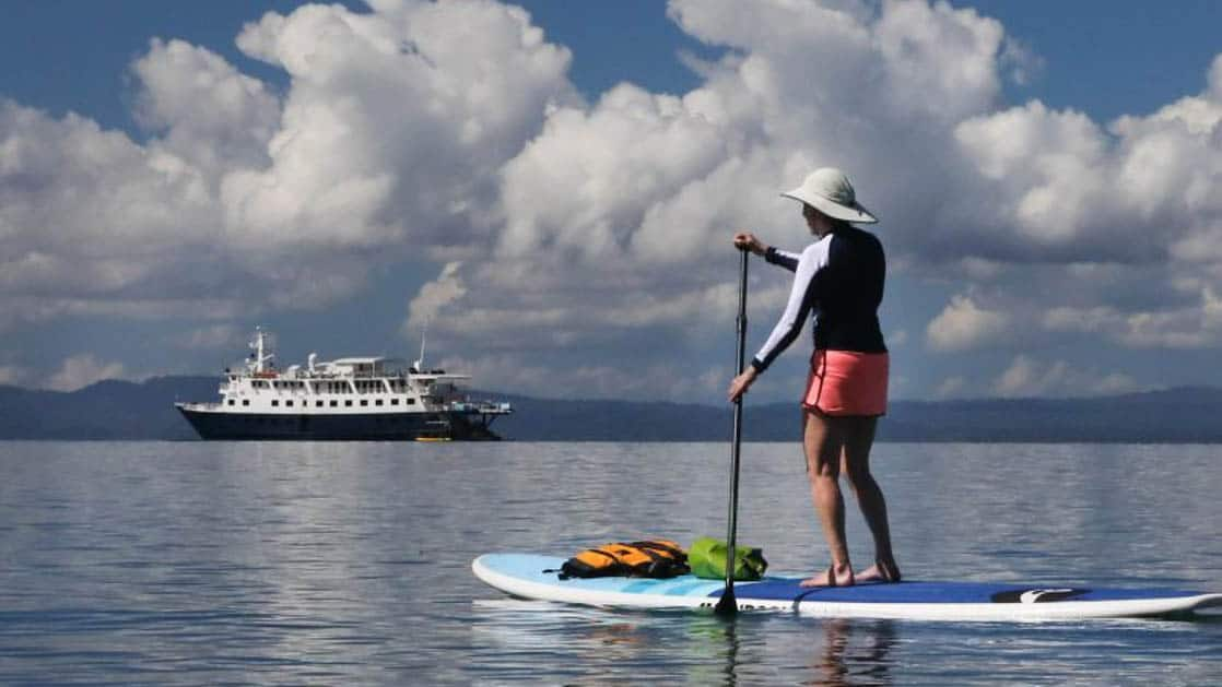 traveler wearing a hat paddleboards in front of a costa rica small ship with puffy clouds above