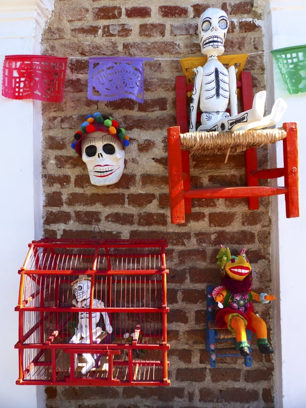 Mexican Day of the Dead masks and skeletons sitting on a chair and in a bird cage on a brick wall with colorful flags.