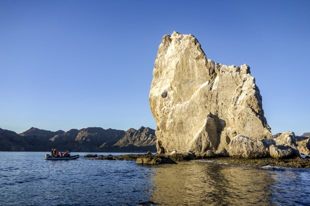 Zodiac with Baja travelers looking at a large rock formation in Baja.