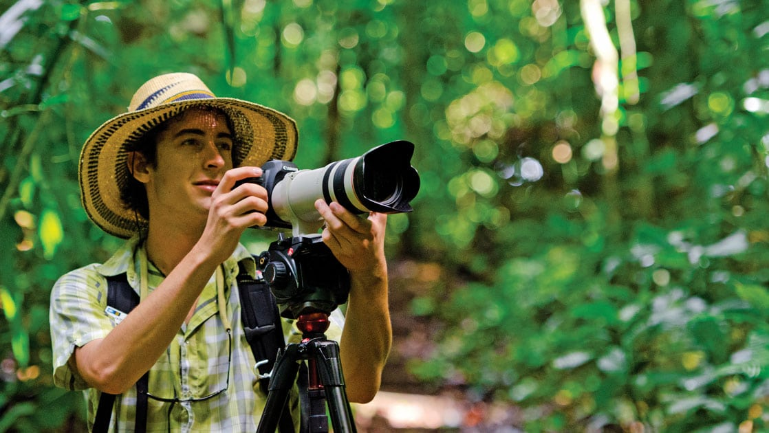 Male traveler uses a large camera on a tripod in the lush green Belize jungle, during the Wild Belize Escape small ship cruise.