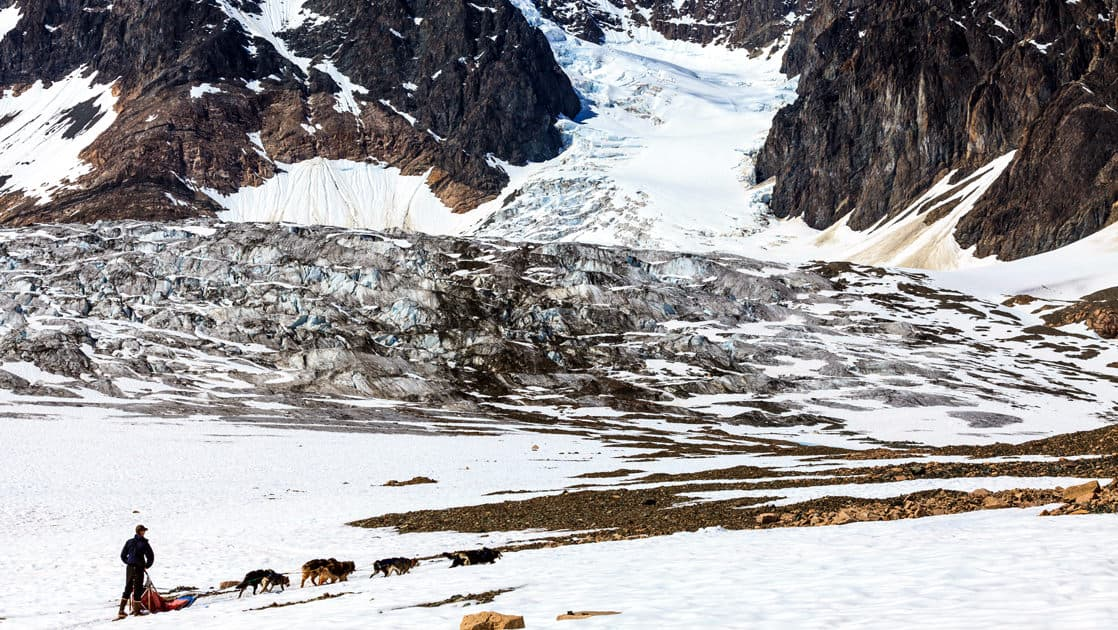 dog mushing camp on top of a glacier with a sled being pulled by a group of dogs