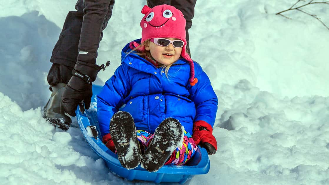kid in a sled being pushed in the snow in alaska