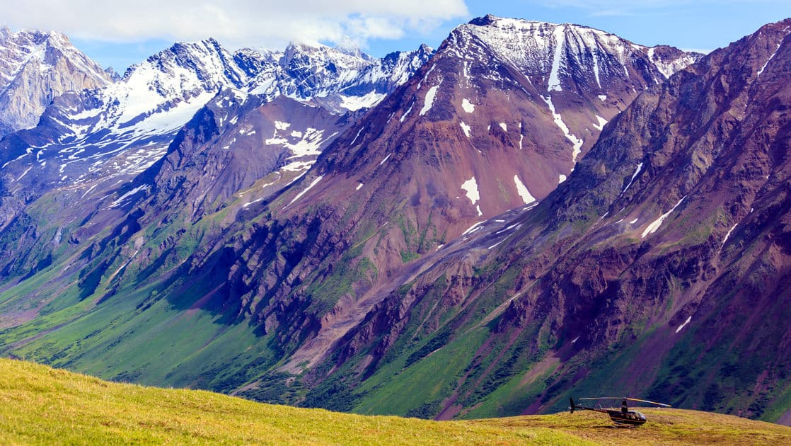 Helicopter landing on a hillside in a very remote region of alaska with tall mountains behind