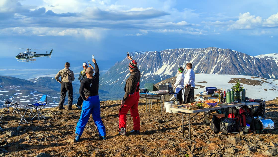group having a picnic at the top of a mountain and cheersing to the helicopter that dropped them off
