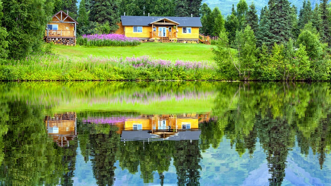 Winterlake lodge in the alaska range with a green lawn in front and a reflection in the still water