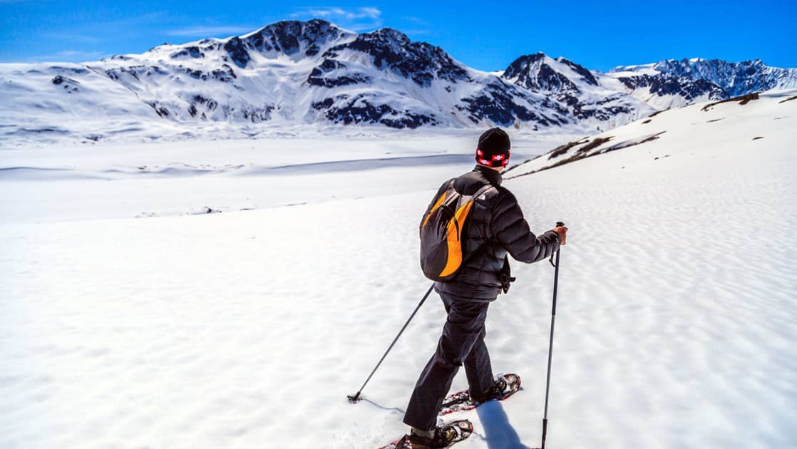 man snowshoeing on top of a glacier in alaska on a sunny day